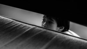 Child hiding behind the bed
