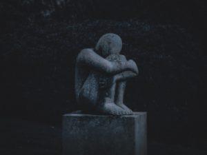 Statue head on knees, sadly