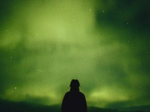 Man standing under the green aurora borealis