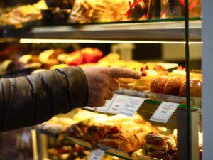 Eligiendo pan y bollos en una panadería