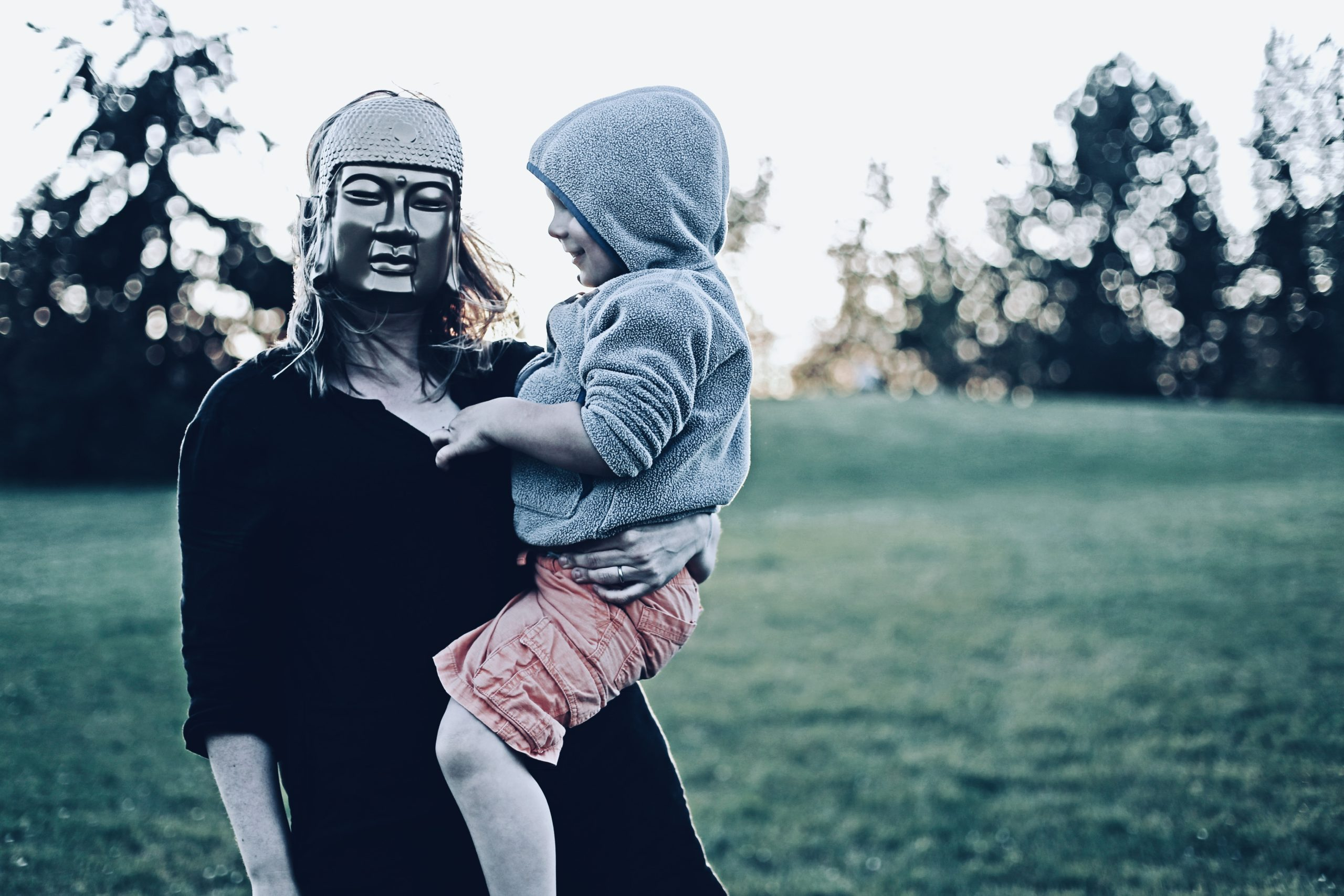 Woman with mask carrying toddler; Fraser River Park, Vancouver, BC