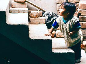 Un niño está jugando en la escalera mientras su madre charla con la gente; Trujillo, Perú