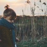 Little girl in brown coat in autumn