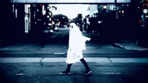 Man in white cloth walking on the road